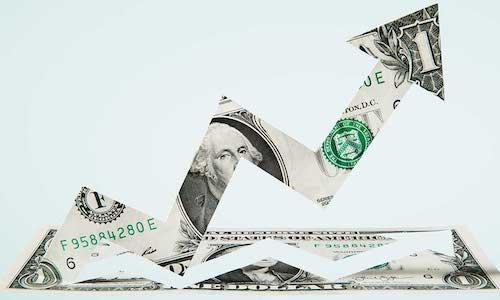 An arrow pointing upwards cut from a U.S. dollar bill.
